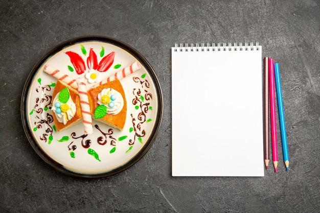 Draufsicht köstliche sahnetorte süße kuchenscheiben innerhalb entworfener platte auf dunklem hintergrund kuchenfarbe süße kekscremetorte