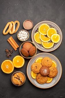 Draufsicht köstliche sandkekse mit frischen orangen auf dunklem hintergrund cookie zucker fruchtkeks süße zitrusfrüchte