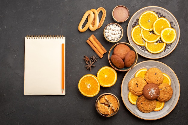Draufsicht köstliche sandkekse mit frischen orangen auf dunklem hintergrund obstkeks süße kekse zitrus