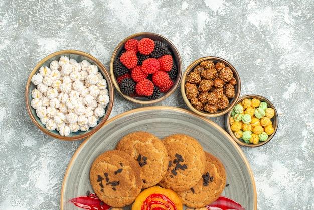 Draufsicht köstliche sandkekse mit keksen und bonbons auf weißem hintergrund keks süßer zuckerkuchen teeplätzchen