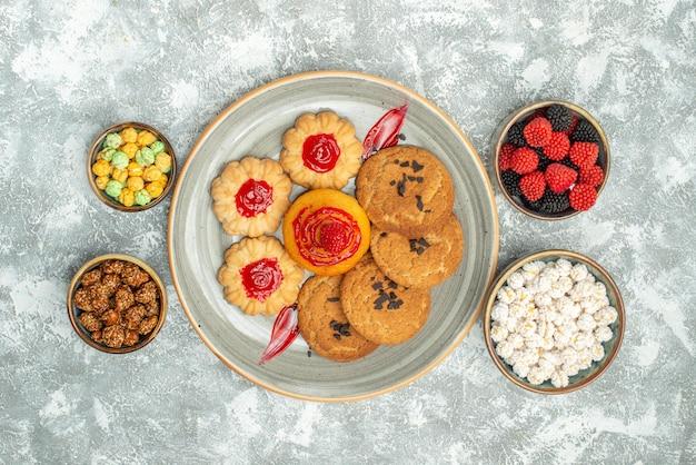 Draufsicht köstliche sandkekse mit keksen und bonbons auf weißem hintergrund zuckerkekskuchen keks tee süß