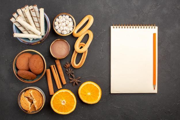 Draufsicht köstliche sandplätzchen mit frischen orangen auf dunklem hintergrund plätzchenzuckerfrucht süßer zitruskeks
