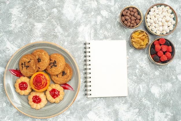 Draufsicht köstliche sandplätzchen mit süßen keksen und bonbons auf weißem hintergrund kuchenplätzchen süßer tee tee