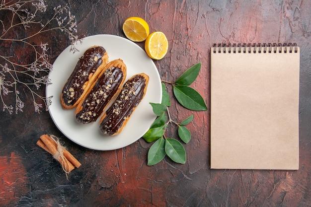 Draufsicht köstliche schoko-eclairs auf dunklen kuchenkuchen des dunklen tischdesserts