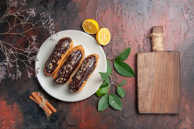 Draufsicht köstliche schoko-eclairs innerhalb des tellers auf süßem nachtisch der dunklen tischkuchen-torte