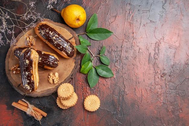 Draufsicht köstliche schoko-eclairs mit keksen auf dunklem tischkuchen süßes dessert