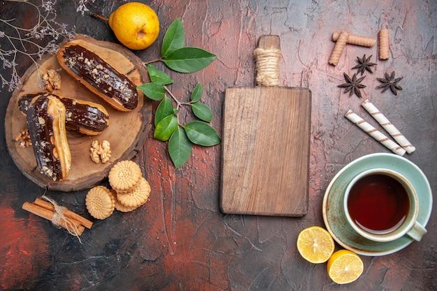 Draufsicht köstliche schoko-eclairs mit tasse tee auf dem dunklen tischdessert süßer kuchen