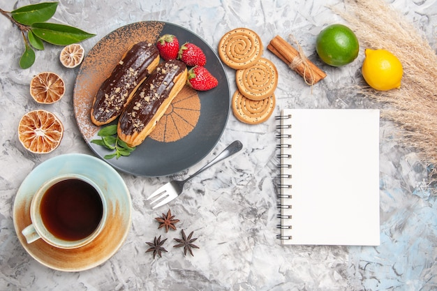Draufsicht köstliche schoko-eclairs mit tee auf dem weißen tischdessertkuchenplätzchen