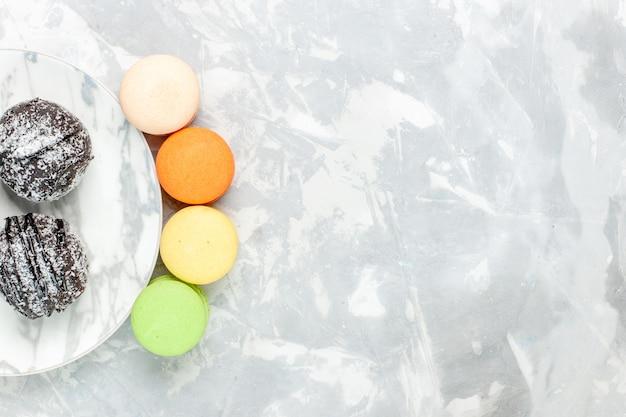 Draufsicht köstliche schokoladenbällchen runde geformte kuchen mit zuckerguss und macarons auf hellweißem schreibtisch backen kuchen schokoladenzuckerkuchen süß