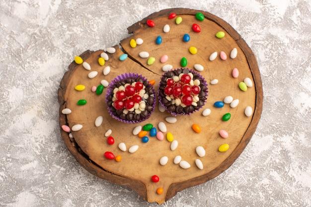 Draufsicht köstliche schokoladenbrownies mit bonbons auf dem hellen hintergrund süßigkeiten goody sugar sweet teig schokolade