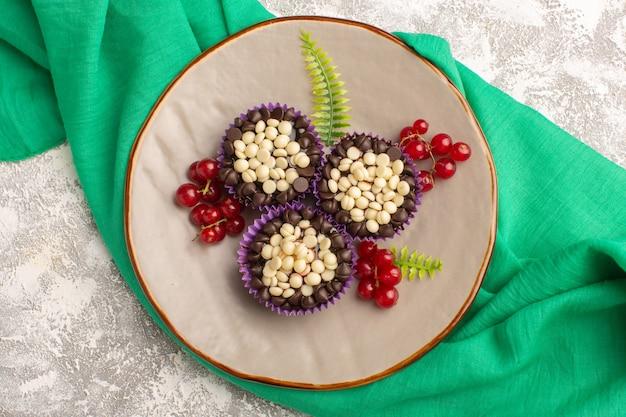 Draufsicht köstliche schokoladenbrownies mit preiselbeeren und schokoladenstückchen auf dem leichten schreibtischkuchenkeks süßer teigauflauf