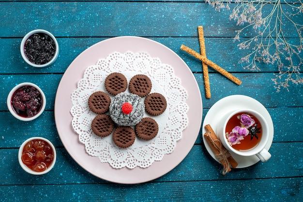 Draufsicht köstliche schokoladenkekse mit marmelade und tasse tee auf dem blauen rustikalen schreibtischkeks-tee-keks süßer kuchenzucker