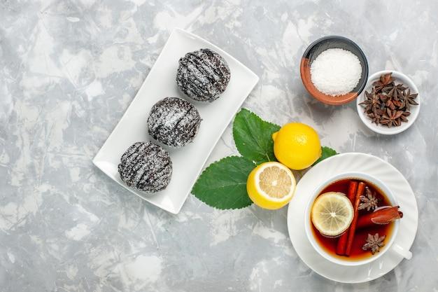 Draufsicht köstliche schokoladenkuchen kleine runde gebildet mit zitrone und tasse tee auf weißer oberfläche obstkuchen keks süßer zucker backen keks