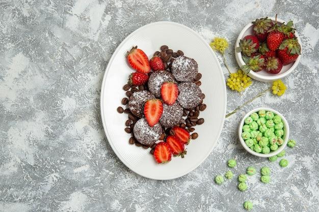 Draufsicht köstliche schokoladenkuchen mit süßigkeiten und erdbeeren auf der weißen oberfläche kekszuckerkuchen süßer tee-keks