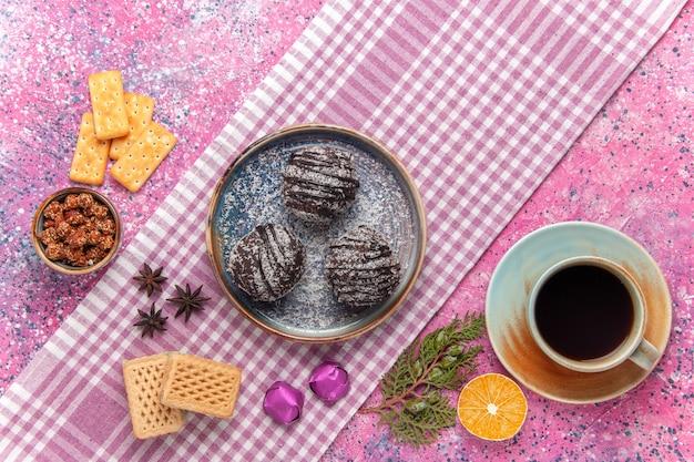 Draufsicht köstliche schokoladenkuchen mit tasse tee und waffeln auf rosa