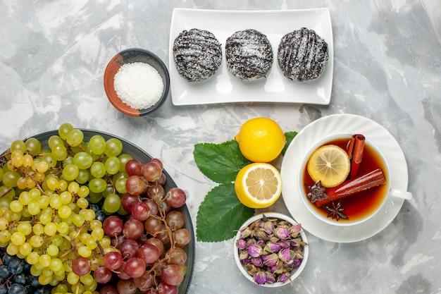 Draufsicht köstliche schokoladenkuchen mit zitronentee und trauben auf weißem oberflächenfruchtkuchenkeks süßem zucker backen keks