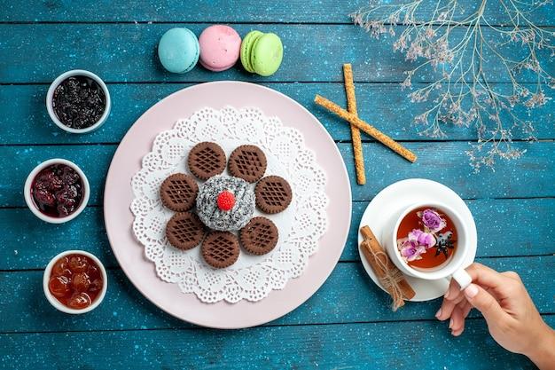 Draufsicht köstliche schokoladenplätzchen mit marmelade und tasse tee auf blauem rustikalem schreibtischkeks-teeplätzchen süßem kuchenzucker