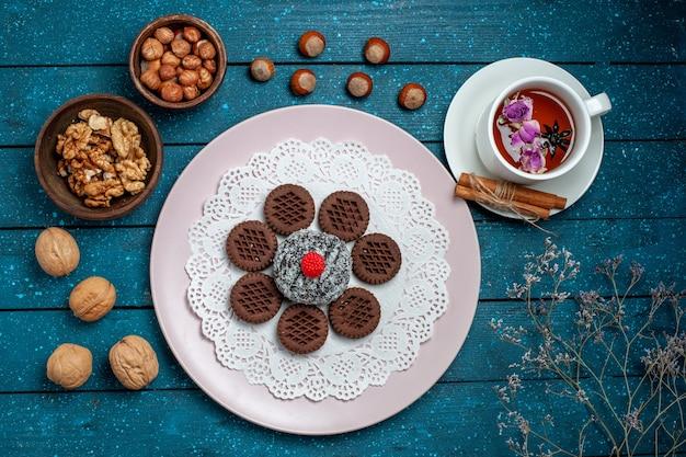 Draufsicht köstliche schokoladenplätzchen mit nüssen und tasse tee auf blauem rustikalem schreibtischkeks-tee-keks süßem kuchenzucker