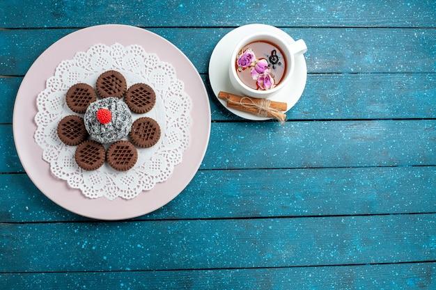 Draufsicht köstliche schokoladenplätzchen mit tasse tee auf blauem rustikalem schreibtischkeks-tee-keks süßem kuchenzucker