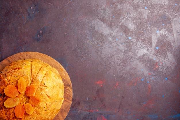 Draufsicht köstliche shakh plov östliche mahlzeit besteht aus gekochtem reis innerhalb des runden teigs auf dunklem hintergrund reisteigmahlzeitessenessen