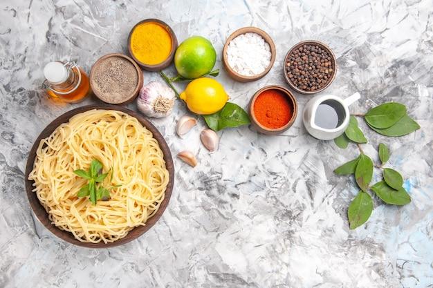Draufsicht köstliche spaghetti mit gewürzen auf weißem nudelteig