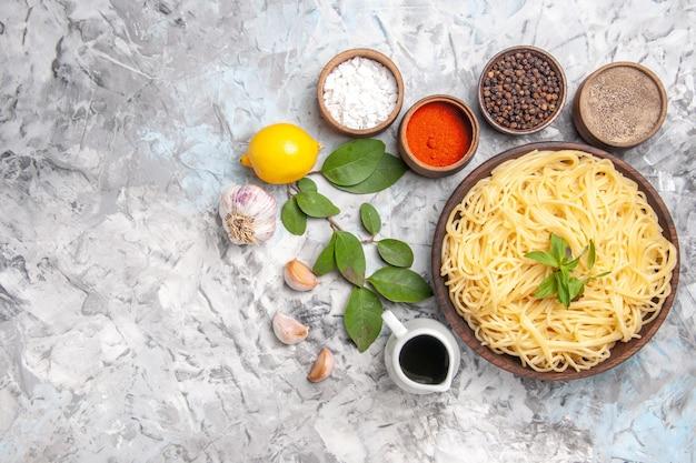 Draufsicht köstliche spaghetti mit gewürzen auf weißem tischabendessenteigmahlzeitnudeln