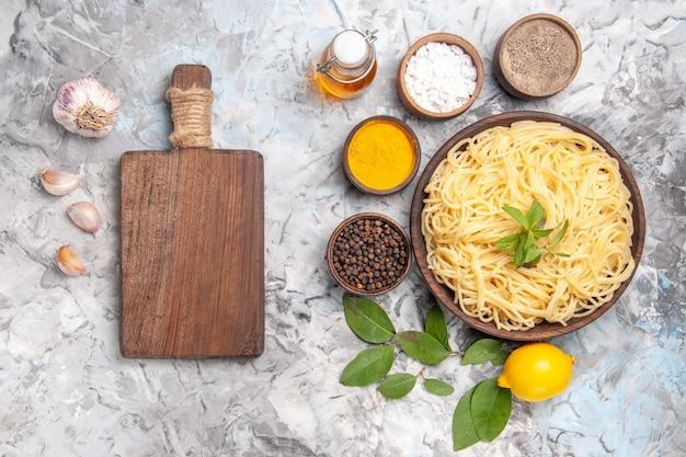Draufsicht köstliche spaghetti mit gewürzen auf weißen tischmehlteignudeln