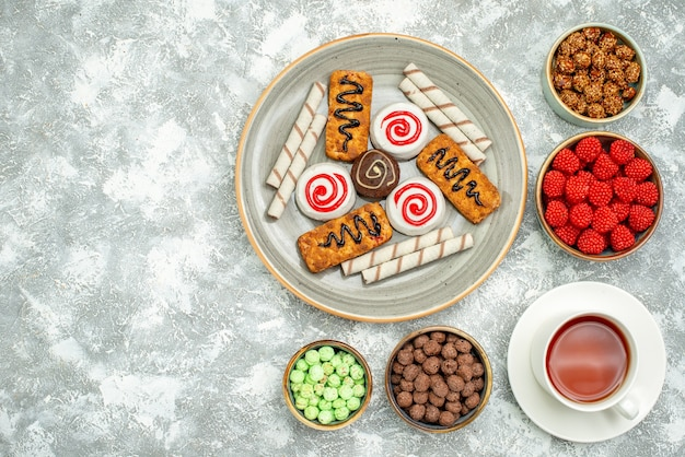 Draufsicht köstliche süße bonbons mit keksen und tasse tee auf weißem raum
