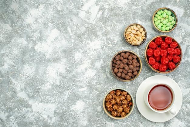 Draufsicht köstliche süße bonbons mit nüssen und tasse tee auf weißem raum
