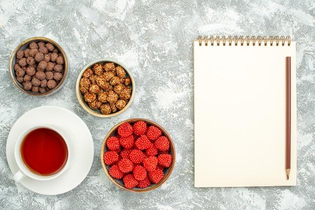 Draufsicht köstliche süße bonbons mit tasse tee auf weißem raum