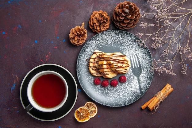 Draufsicht köstliche süße brötchen geschnittener kuchen für eine tasse tee auf dem dunklen hintergrund rollenkeks süße torte kuchen tee dessert