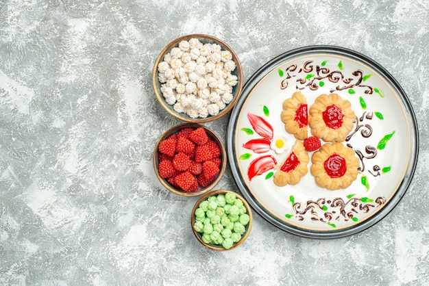Draufsicht köstliche süße kekse mit bonbons auf dem weißen hintergrundkuchen süßer keksplätzchentee