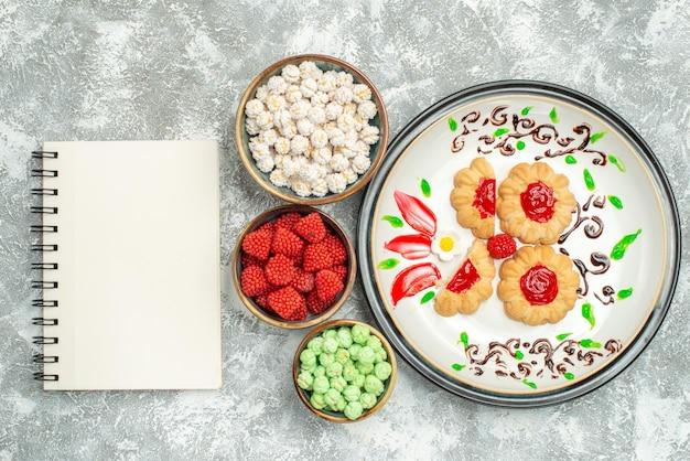 Draufsicht köstliche süße kekse mit bonbons auf hellweißem hintergrund kuchen süßer keksplätzchentee