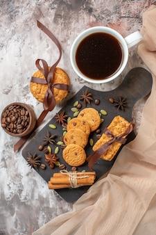 Draufsicht köstliche süße kekse mit kaffeesamen und tasse kaffee auf hellem hintergrund zuckerteeplätzchen süße kakaokuchenfarbe