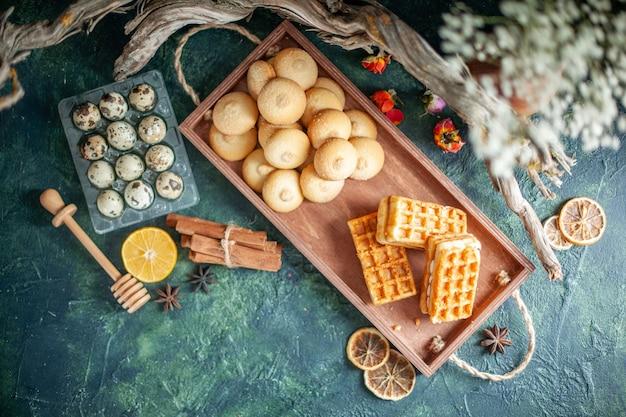 Draufsicht köstliche süße kekse mit kleinen kuchen auf dunkler oberfläche