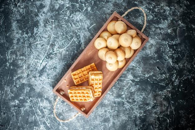 Draufsicht köstliche süße kekse mit kleinen kuchen auf grauer oberfläche