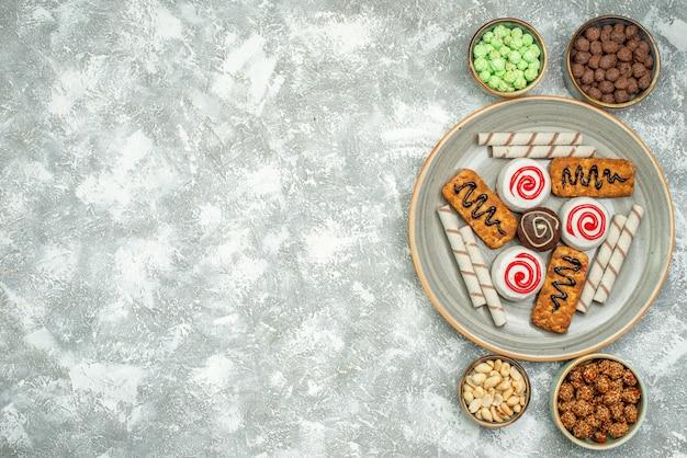 Draufsicht köstliche süße kekse mit kuchen und süßigkeiten auf weißem raum