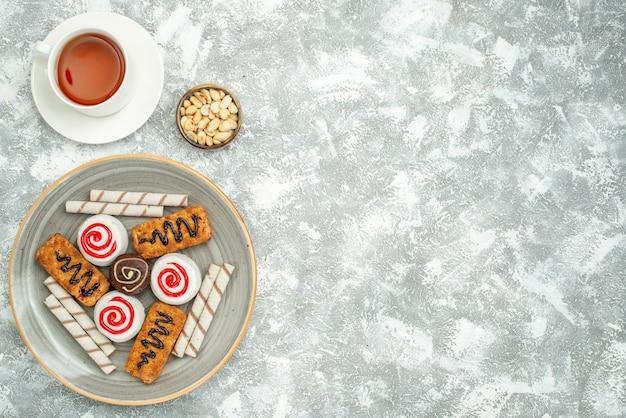 Draufsicht köstliche süße kekse mit kuchen und tee auf weißem raum