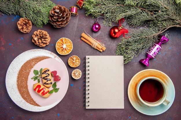 Draufsicht köstliche süße kekse mit tasse tee und weihnachtsbaum auf dunklem hintergrund cookie süßer keks zuckerfarbe kuchen