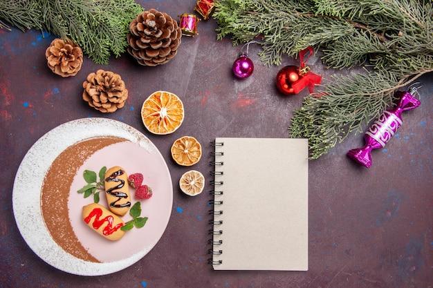 Draufsicht köstliche süße kekse mit weihnachtsspielzeug und baum auf dunklem hintergrundplätzchen süßer kekszuckerfarbenkuchen