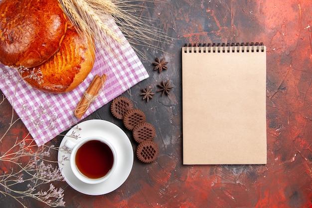Draufsicht köstliche süße kuchen mit tasse tee auf dem dunklen tischkuchen süßes kuchengebäck