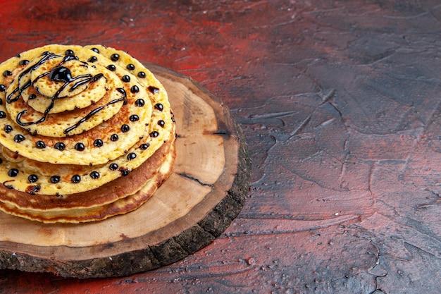 Draufsicht köstliche süße pfannkuchen mit zuckerguss auf der dunklen oberfläche