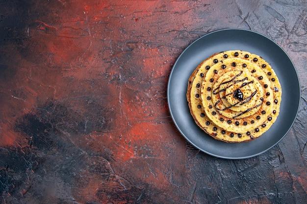 Draufsicht köstliche süße pfannkuchen mit zuckerguss auf dunklem schreibtisch