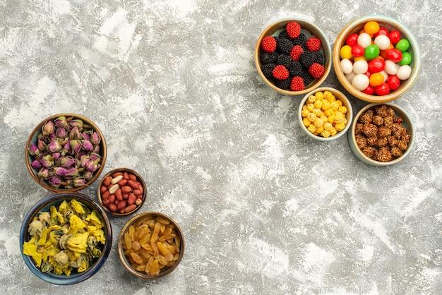 Draufsicht köstliche süßwaren mit süßigkeiten getrockneten blumen und nüssen auf weißem hintergrund süßigkeitsnusszuckerplätzchen