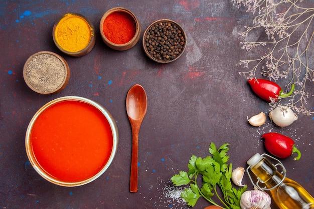Draufsicht köstliche tomatensuppe gekocht aus frischen tomaten mit gewürzen auf dunklem hintergrund tomatengericht suppe soße mahlzeit rot