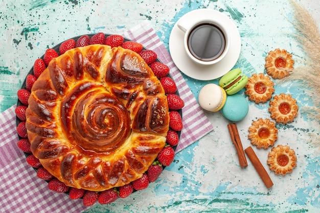 Draufsicht köstliche torte mit erdbeer-macarons und tasse tee auf der blauen oberfläche