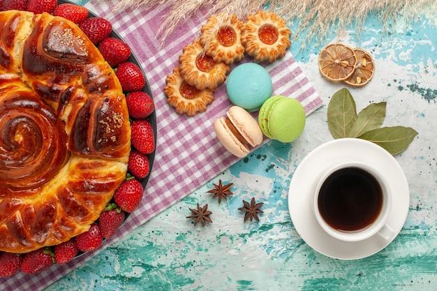 Draufsicht köstliche torte mit erdbeeren und tasse tee auf blauer oberfläche