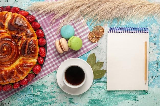 Draufsicht köstliche torte mit erdbeeren und tasse tee auf hellblauer oberfläche