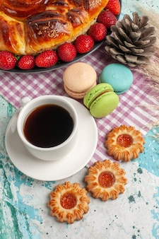Draufsicht köstliche torte mit frischen roten erdbeeren macarons und tasse tee auf der blauen oberfläche