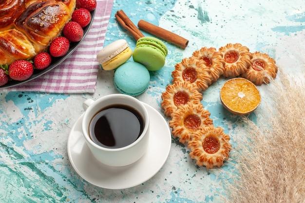 Draufsicht köstliche torte mit frischen roten erdbeeren macarons und tasse tee auf hellblauer oberfläche